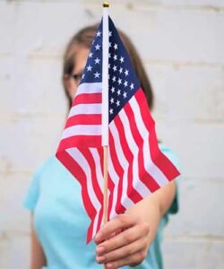 Woman holding an American flag (Photo by twinsfisch on Unsplash)